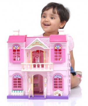 A young child playing with a Barbie Dreamhouse.