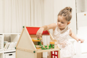 girl playing with wooden doll house