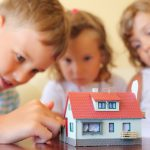 Kids playing with small dollhouse