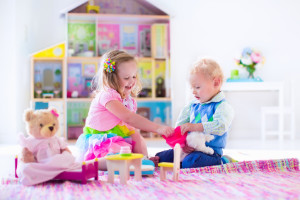 boy and girl sitting in front of dollhouse